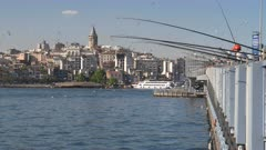 low angle view of fishermen on galata bridge with galata tower in the background at istanbul, turkey