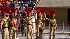 indian border guards throw up their arms in challenge to the pakistani guards at the wagah border in amritsar, india