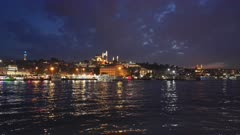 night shot of the ferry terminal and rustem pasha mosque on the waterfront of istanbul, turkey