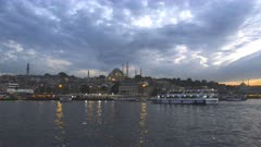 4K 60p dusk clip of a commuter ferry approaching a pier with a pasha rustem mosque in the distance at istanbul, turkey