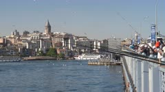 crowd of fishermen on galata bridge with galata tower in the distance at istanbul, turkey