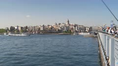 a wide angle view from galata bridge of the tower and fishermen in istanbul, turkey