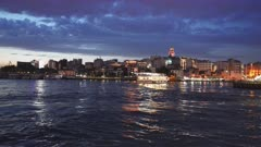 night view of galata tower and a ferry about to dock in istanbul, turkey