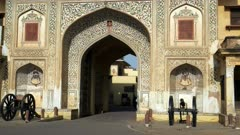 wide view of archway with antique cannon at the entrance to city palace in jaipur, india