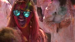 a girl wearing blue sunglasses greets a friend during holi celebrations in jaipur, india
