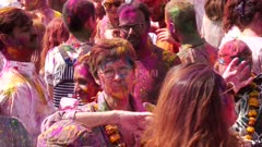 a mature aged woman with floral garland dances at a holi party in jaipur, india