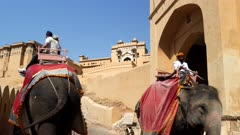 an uphill shot of tourists riding elephants at amer fort in jaipur, india