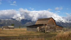 mormon row barns with autumn snow and clouds at grand teton national park in wyoming, usa