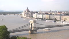 a tour boat sails under chain bridge in budapest, hungary