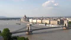 wide angle zoom in view of chain bridge and the hungarian parliament building in budapest, hungary