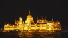 night time side on view of the hungarian parliament and a tour boat in budapest, hungary