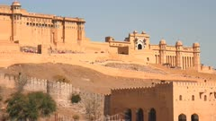wide shot of elephants carrying tourists climbing a ramp to amber fort in jaipur, india