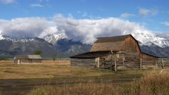 pan of moulton barn with early autumn snow on the mountains of grand teton national park in wyoming, usa