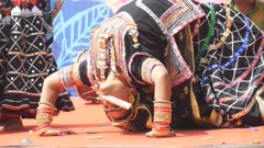 a female dancer bends over backwards a picks up a rupee note with her mouth at a holi celebration in jaipur, india