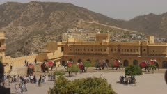 elephants unload their riders in the main square at amber fort in jaipur, india