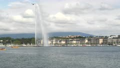 yellow ferry boats sail past the fountain on lake geneva in the city of geneva, switzerland