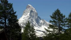 close up zoom in on the summit of the matterhorn mountain framed by pine trees at zermatt, switzerland