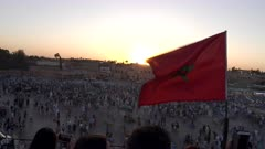 sunset shot of the moroccan flag flying above the jemaa el-fnaa bazaar in marrakesh, morroco