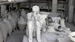 plaster cast of a victim in a sitting position at pompeii ruins near naples, italy
