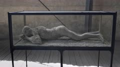 pan of a plaster cast of a woman victim, in a glass case, at pompeii ruins near naples, italy