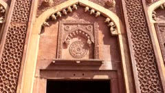 zoom in on an ornately decorated doorway at red fort in agra, india