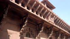 panning shot of ornately carved eaves on a building at red fort in agra, india