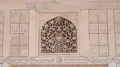 zoom in on an ornately carved ventilation screen above a door at red fort in agra, india