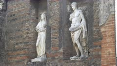 pan of two marble statues at pompeii ruins near naples, italy