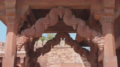 high frame rate tilt up shot of an ornately carved doorway at fatephur sikri near agra, india