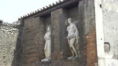 wide shot of two marble statues at pompeii ruins near naples, italy
