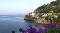 morning view of a village on the amalfi coast with purple bougainvillea flowers in the foreground