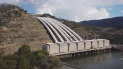 aerial ascending view of talbingo dam inlet pipes and power station in the snowy mountains of nsw, australia