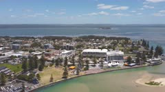 an aerial ascending midday shot of the entrance waterfront on the nsw central coast of australia