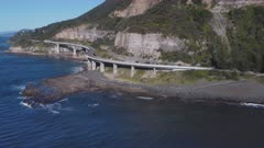 wide aerial view of sea cliff bridge, flying forwards towards the south, on the nsw south coast of australia