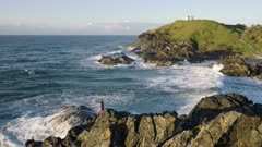 early morning shot of a fisherman rock fishing near tacking point lighthouse at port macquarie in nsw, australia