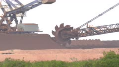 close up of an iron ore bucket wheel reclaimer in operation at port hedland in western australia