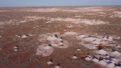 an aerial shot flying forward over opal mines and mullock heaps at coober pedy in outback south australia