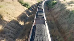 an overhead shot of train wagons loaded with coal in the upper hunter valley heading to the port of newcastle in nsw, australia