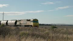 an approaching train with wagons of coal heads to the port of newcastle in nsw, australia