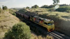 a high angle shot of a coal train, in upper hunter valley, approaching and heading to the port of newcastle in nsw, australia- recorded with with lens flare