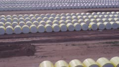 an ascending  aerial clip of rows of cotton bales to be processed by a cotton gin at trangie in western nsw, australia