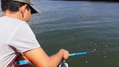 A young angler catching a blenny (then release it)