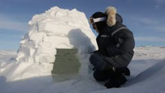Man crawling inside of a small igloo