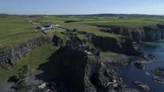 Ireland, aerial view of Dunluce castle with Antrim coastline, backlit circular move