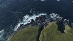 Aerial view of Donegal coastline with rocky reefs, Ireland, top down move closer