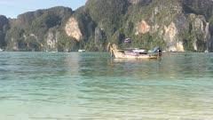 4K -25min anchored fishing boat against island cliffs
