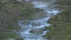 Southern Iceland. Mountain stream steaming from hot geyser upstream. Reykjadalur valley near Hveragerdi.