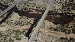 Aerial Eagle Canyon Bridge transportation Utah desert overhead. Double span interstate I-70 highway crosses deep gorge. Travel traffic overhead drone view. San Rafael Reef is a geologic feature in central Utah. Eroded into tall fins, domes, cliffs, and deep canyons.  Hikers, backpackers, horseback riders, and 4x4 all terrain vehicle ( ATV and SxS ), off road enthusiasts enjoy recreation. Dangerous wilderness desert environment. 4K HD video footage. Despain Rekindle Photo. 147
