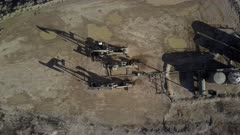 Aerial overhead oil field pump and storage. Oil rig, pumps and storage structure with industrial facilities to drill wells, extract and process crude oil and natural gas. Store product until it can be transported to refining and marketing. Accidents and pollution spills damage environment. Mountain valley Utah. 4K footage video.  Despain Rekindle Photo. 915