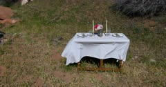 Dining room formal table dinner outdoors. Formal table setup in nature for a romantic date with spouse, husband or wife. Plates, white cloth, napkins, flowers, candles and wine glass. Near river and picnic camping area park. Love and friendship. Memory. 4K HD video footage. Despain Rekindle Photo. 5376